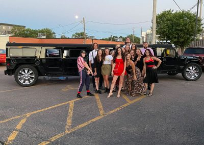 Group of happy people standing in front of limo.